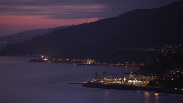 Malibu coastline and Pacific Coast Highway at dusk, car lights race along curving coastline