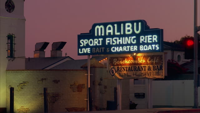 t/l ws 'malibu pier' neon sign, dusk to night, malibu, california, usa - malibu stock videos & royalty-free footage