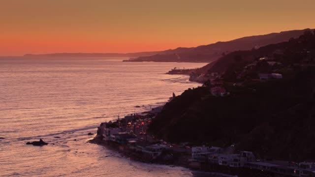 malibu silhouetted against orange sunset - drone shot - malibu stock videos & royalty-free footage