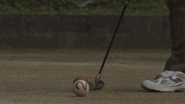 Mallet hits ball sending it out of shot. Japan.