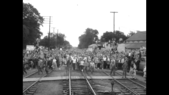 mamie eisenhower holding bouquet of flowers waves from rear platform of train / vs pov crowd of townspeople following the train side of train... - dwight eisenhower video stock e b–roll