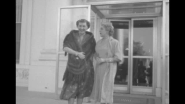 mamie eisenhower wearing fur wrap and mary pickford come out of door and stand for photo opportunity as wind blows / woman appears and hands... - first lady stock-videos und b-roll-filmmaterial