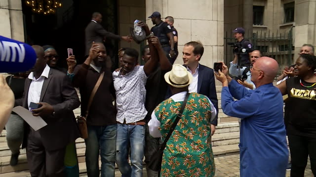 mamoudou gassama, dubbed 'spiderman' after rescuing a small boy who was dangling from a balcony, being met by photographers and wellwishers in paris,... - ヒーロー点の映像素材/bロール