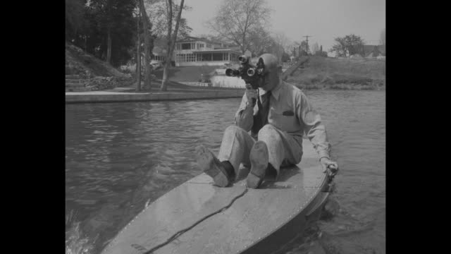 VS man 50s with a movie camera shoots film as he sits on moving Motorboard designed by Hollywood inventor Joe Gilpin docks and houses stand in bkgd...