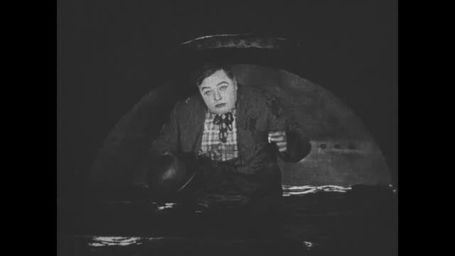 1918 Man (Fatty Arbuckle), a drifter, rides in a train's water tank and spills water on his head when he puts his hat on