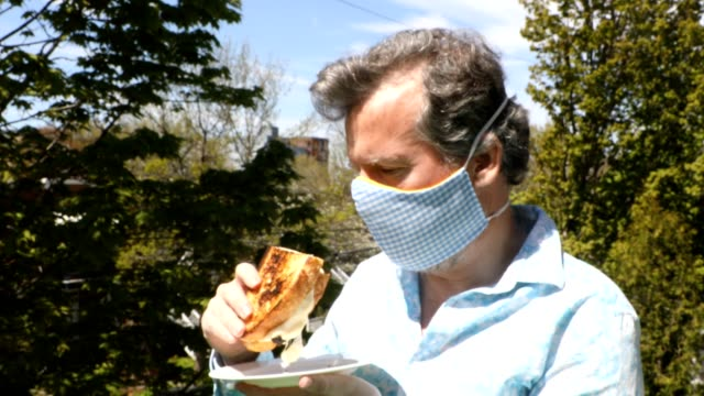 man about to eat a fresh homemade grilled cheese realizes he is still wearing a mask - satire stock videos & royalty-free footage