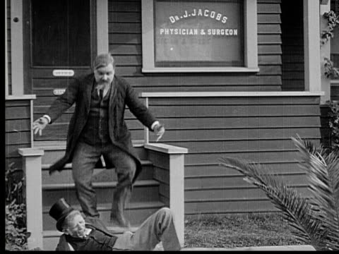 1913 b/w ws man (fatty arbuckle) accidentally hits old man who falls off porch, then old man fights back with his cane / usa - slapstick stock videos & royalty-free footage