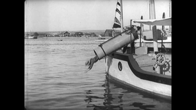 1921 man (buster keaton) accidentally places ship's horn over son before tipping him into the water - 1921年点の映像素材/bロール