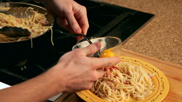 POV man adding parmesan cheese and eggs to pasta