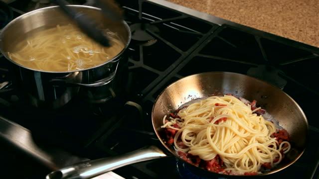 pov man adding pasta to cooked bacon - fleischzange stock-videos und b-roll-filmmaterial