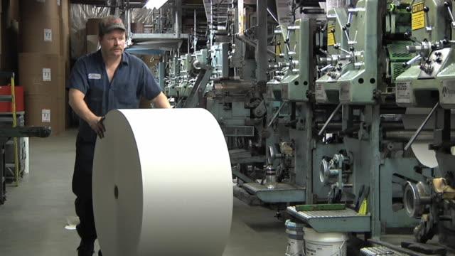 WS Man adding roll of newsprint to press at printing plant / Powers, Michigan, USA