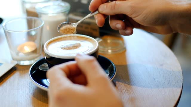 mann hinzufügen von zucker in kaffee im café - zucker stock-videos und b-roll-filmmaterial