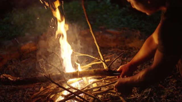 slo mo - 男は焚き火で森を調整します - 外乗点の映像素材/bロール