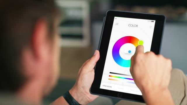 スマートホームで光の色を調整する男性 - コントロール点の映像素材/bロール