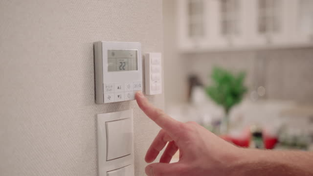 vídeos de stock e filmes b-roll de man adjusting digital thermostat - morno