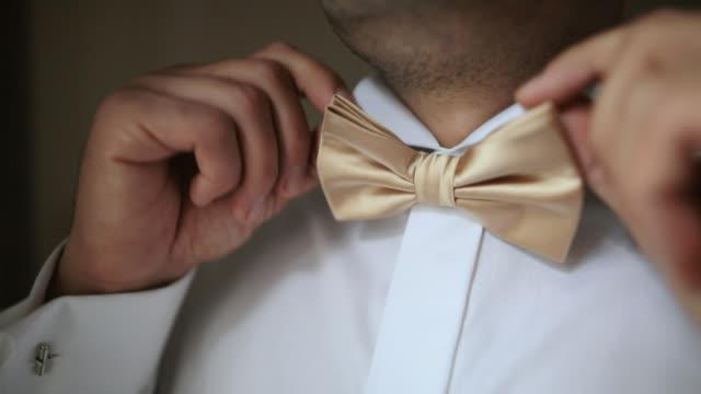 vidéos et rushes de homme ajustant son noeud papillon sur la chemise blanche - shirt and tie