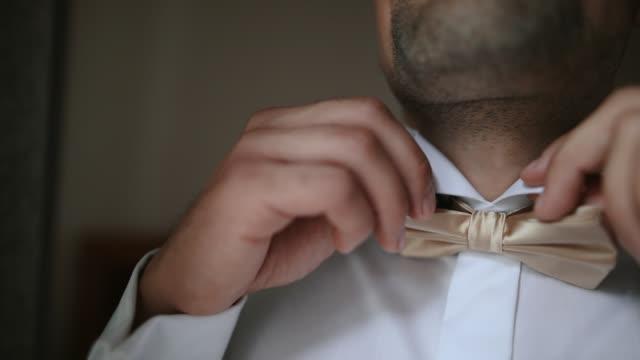 vidéos et rushes de homme ajustant son noeud papillon sur la chemise blanche - noeud papillon