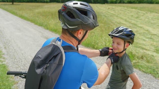 cs man adjusting his son's bike helmet and they start cycling up the beautiful sunny mountain valley - cycling helmet stock videos & royalty-free footage