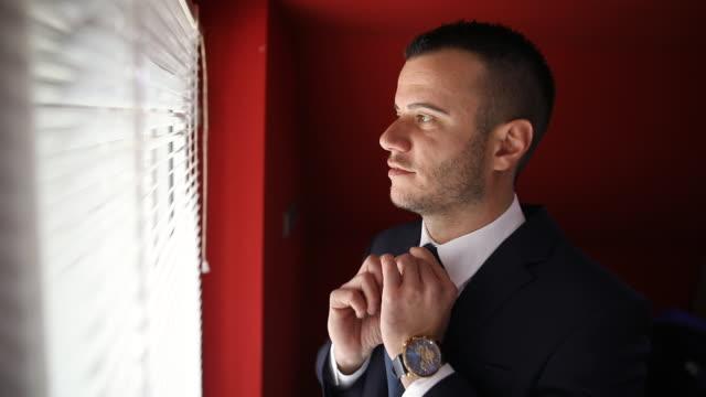 vídeos y material grabado en eventos de stock de hombre ajustando corbata mientras está de pie cerca de la ventana en la sala de estar y mirando la cámara - cuello parte de la vestimenta