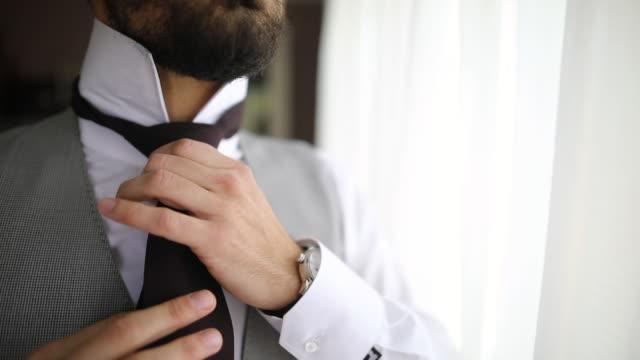 vidéos et rushes de l'homme ajustant la cravate tout en restant près de la fenêtre dans le salon - vêtement de peau