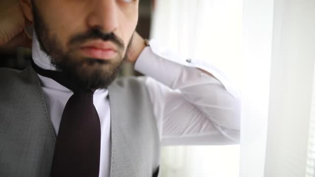 man adjusting necktie while standing near window in living room - metrosexual stock videos & royalty-free footage
