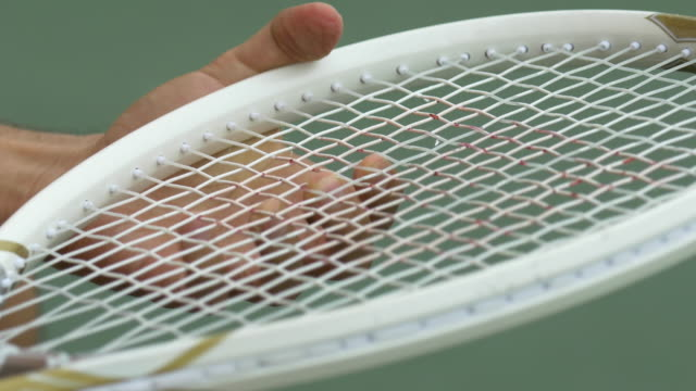 man adjusting the strings on a tennis racket. - tennis racquet stock videos & royalty-free footage