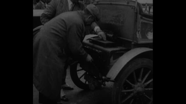 cu man adjusts boiler on rear of steampowered car flames shoot out / two men close boiler and insert and turn crank / men get into the car with a... - passing a note stock videos and b-roll footage