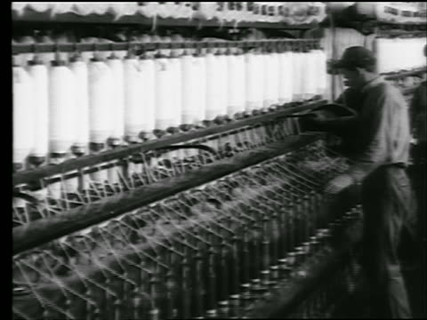 B/W 1922 man adjusts machinery on spinning bobbins with cotton thread in cotton mill / newsreel