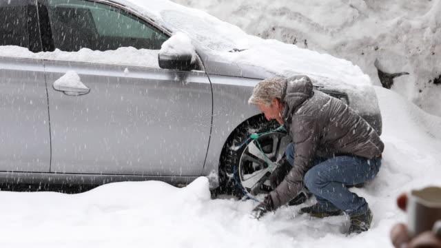 vidéos et rushes de l'homme s'adapte chaînes à neige sur pneus de voiture - chaîne