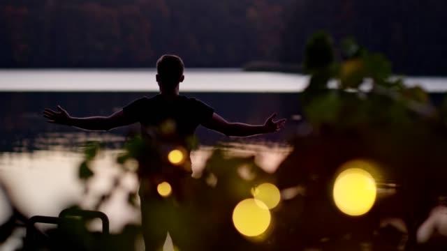 vídeos y material grabado en eventos de stock de hombre admirando lago puesta de sol. brazos abiertos - brazo humano