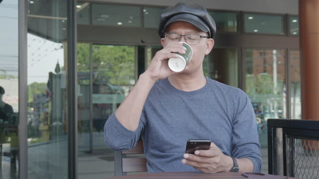 man age 40-50 year with smartphone and coffee drink in coffeeshop - coffee drink stock videos & royalty-free footage
