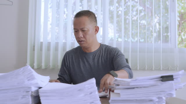 mann im alter von 40-50 jahren in freizeitkleidung sitzt am schreibtisch voller dokumente bei der arbeit. - akte stock-videos und b-roll-filmmaterial