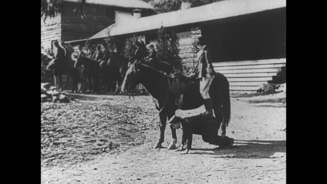 1921 man (buster keaton) allows a woman (virginia fox) to step on his back to get onto a horse - 1921年点の映像素材/bロール