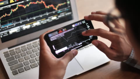 a man analyzing looking stock market on smart phone - blockchain stock videos & royalty-free footage