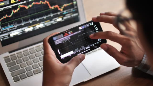 a man analyzing looking stock market on smart phone - market trader stock videos & royalty-free footage