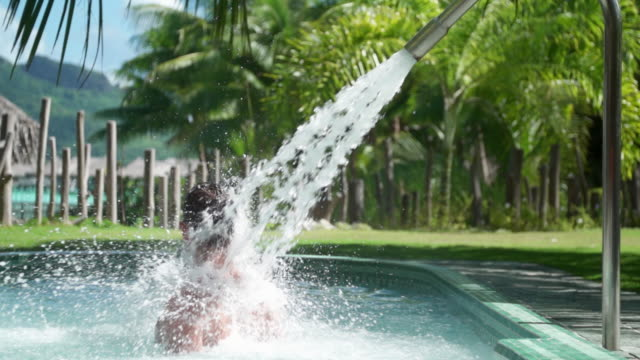 A man and a hot tub jacuzzi spa pool, lifestyle at a tropical island resort. - Slow Motion