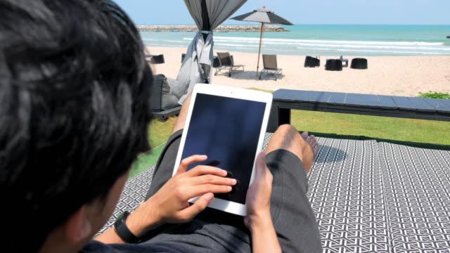 ein mann mit einem laptop sitzt am strand-bett - schiebermütze stock-videos und b-roll-filmmaterial
