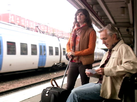 a man and a woman at a train station stockholm sweden. - three quarter length stock videos & royalty-free footage