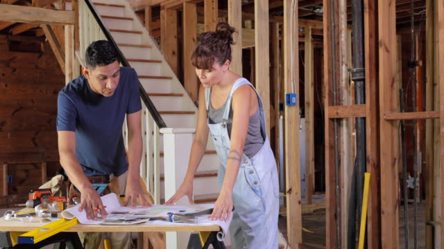 a man and a woman discuss design plans on home renovation. - bib overalls stock videos and b-roll footage
