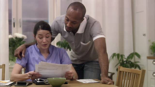 A man and a woman doing paper work at home Sweden.