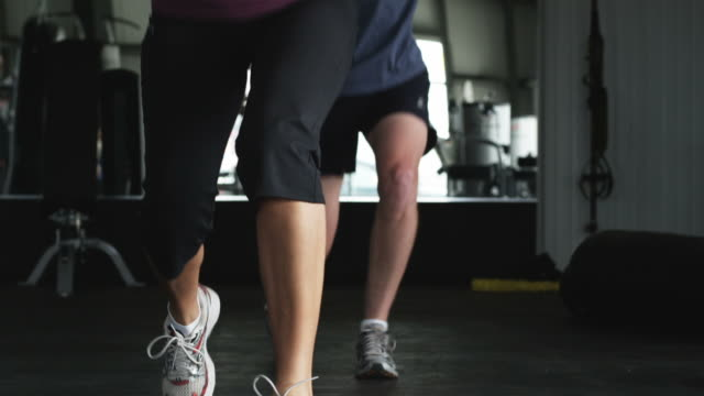 vidéos et rushes de man and a woman doing squats in a gym - cadrage en pied
