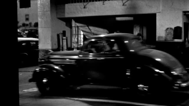 a man and a woman exit a chauffeur-driven sedan in a car repair garage in 1935. - chauffeur stock videos & royalty-free footage