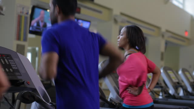 a man and a woman keep pace with each other as they run on treadmills. - treadmill stock videos and b-roll footage