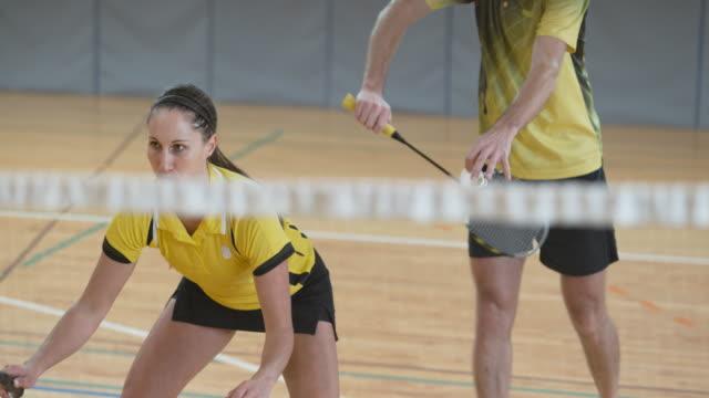 vidéos et rushes de un homme et une femme jouant badminton doubles - badminton sport