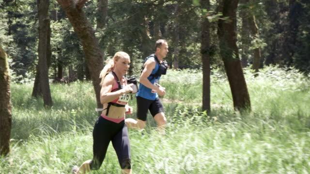 SLO MO DS Man och en kvinna som ett maratonlopp genom skogen