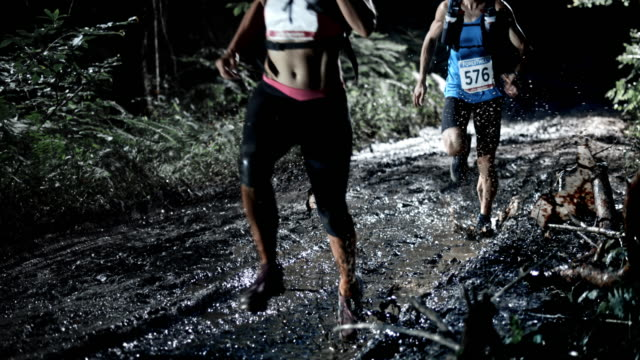 slo mo ds man and a woman running a night trail marathon - leanincollection stock videos & royalty-free footage