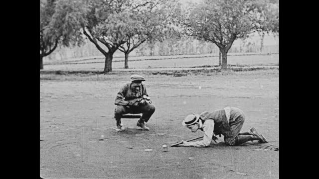 vídeos y material grabado en eventos de stock de 1920 man (buster keaton) and attractive woman (sybil seely) play golf - golf cart
