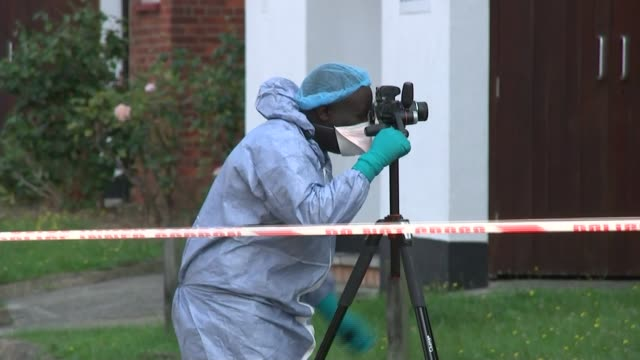 man and aunt shot dead in east finchley england london finchley ext various of police officers and forensics officers outside flat where bervil ekofo... - finchley stock videos and b-roll footage
