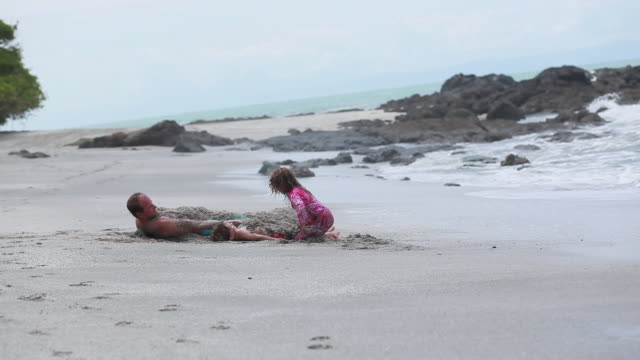 ms man and boy lie on sand and are covered with sand while girl covers boy with sand / montezuma, puntarenas, costa rica - kelly mason videos stock videos & royalty-free footage