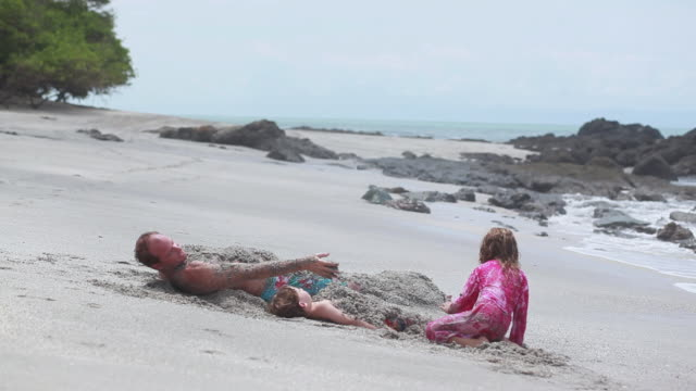 ms man and boy lie on sand covered in sand while man and girl cover boy with sand then boy sits up on beach / montezuma, puntarenas, costa rica - kelly mason videos stock-videos und b-roll-filmmaterial